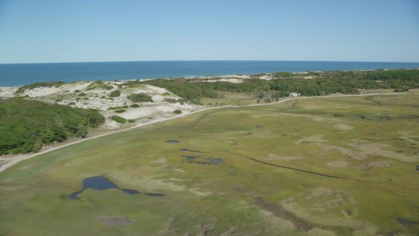 Flying by marshland, isolated homes, coastal road, Barnstable, Massachusetts Aerial Stock Footage   AX143_137