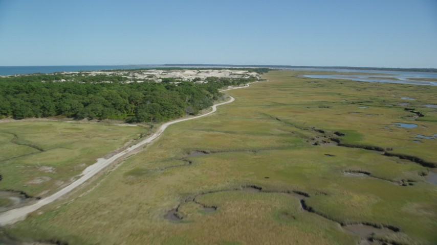Flying over coastal road, marshland, sand dunes, Barnstable, Massachusetts Aerial Stock Footage | AX143_138