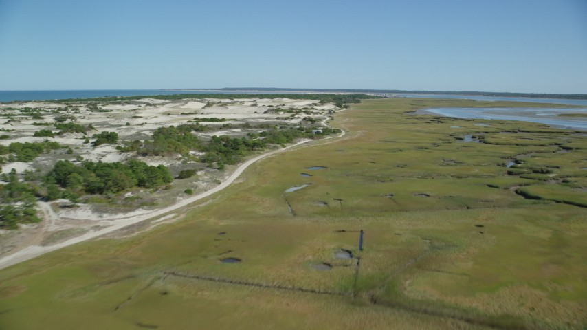 6K aerial video flying over coastal road, marshland, sand dunes, Barnstable, Massachusetts Aerial Stock Footage | AX143_138
