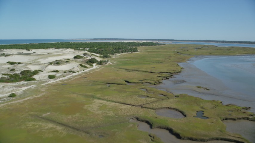 6K aerial video of an isolated home, coastal road, marshland, sand dunes, Barnstable, Massachusetts Aerial Stock Footage | AX143_139