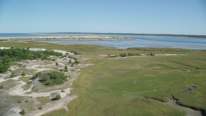 Fly over marshland, approach Sandy Neck Colony, Barnstable, Massachusetts Aerial Stock Footage | AX143_142