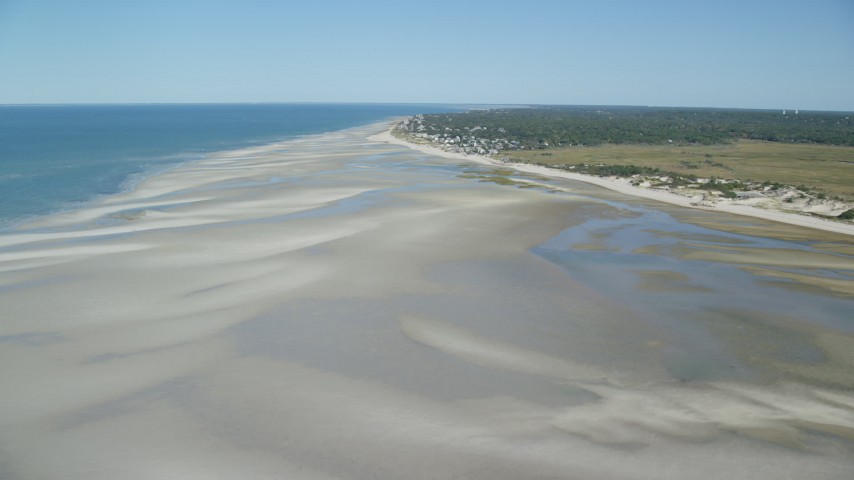 Fly over sand bars, approach small coastal town, Cape Cod, Dennis, Massachusetts Aerial Stock Footage | AX143_150
