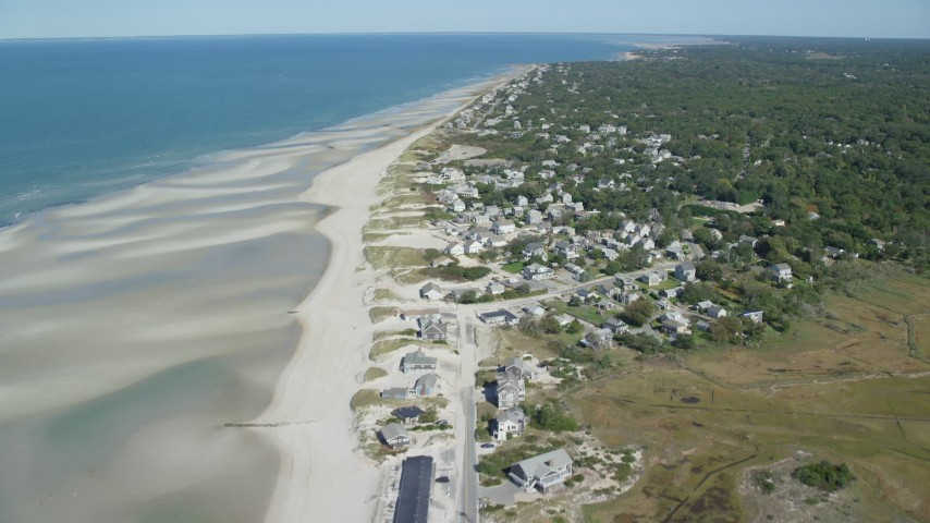 Fly over sand bars, approach small coastal town, Cape Cod, Dennis, Massachusetts Aerial Stock Footage AX143_151