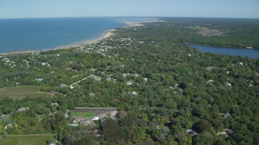 Flying over small coastal town, green trees, Cape Cod, Dennis, Massachusetts Aerial Stock Footage | AX143_154