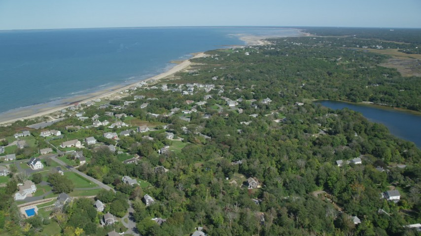 Flying over small coastal town, pan left to beach, Cape Cod, Dennis, Massachusetts Aerial Stock Footage | AX143_155