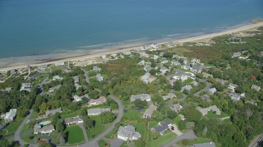 Flying by beachfront homes, small town, Cape Cod, Dennis, Massachusetts Aerial Stock Footage | AX143_156