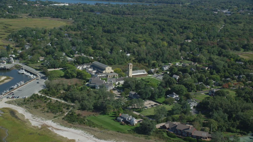 6K stock footage aerial video flying by small coastal town, Church of the Transfiguration, Orleans, Massachusetts Aerial Stock Footage AX143_180 | Axiom Images