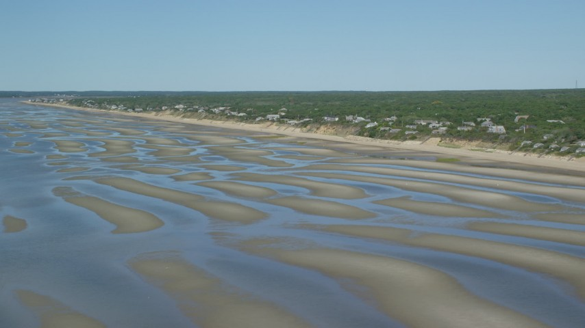 6K aerial video flying over sand bars and by beachfront homes, Eastham, Massachusetts Aerial Stock Footage | AX143_183