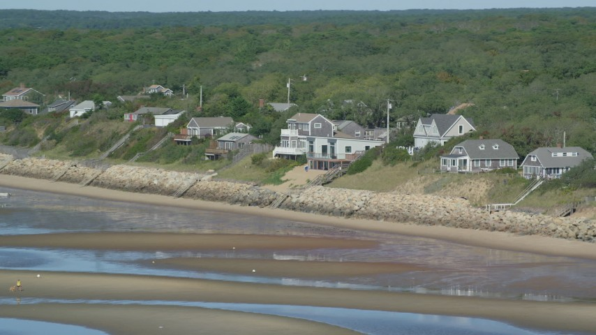 Flying by raised beachfront homes, Cape Cod, Eastham, Massachusetts Aerial Stock Footage | AX143_185