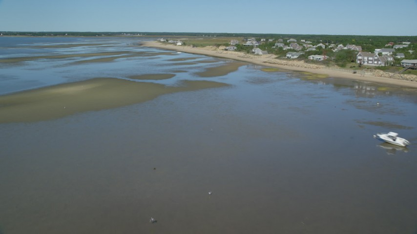 Flying over sand bar, by beachfront homes, Cape Cod, Eastham, Massachusetts Aerial Stock Footage | AX143_188