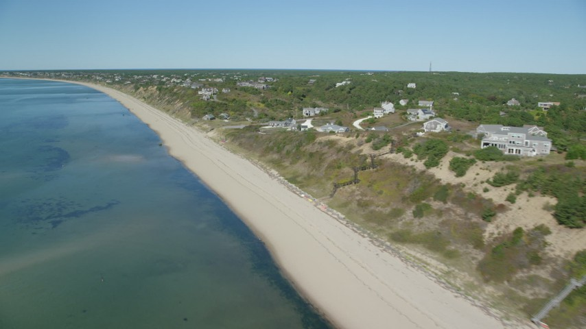 6K aerial video flying by beach, homes with ocean views, Cape Cod, Truro, Massachusetts Aerial Stock Footage | AX143_208