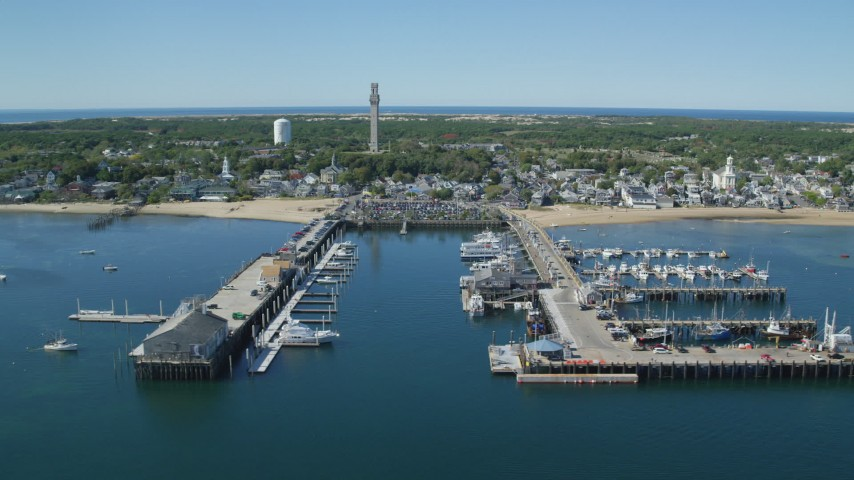 6K stock footage aerial video flying by piers, small coastal town, Cape Cod, Provincetown, Massachusetts Aerial Stock Footage | AX143_223