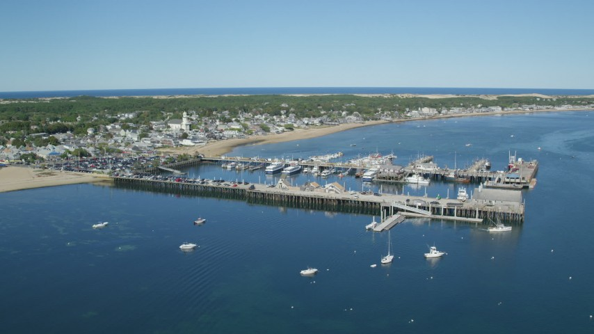 6K stock footage aerial video orbiting piers near small coastal town, Cape Cod, Provincetown, Massachusetts Aerial Stock Footage | AX143_225