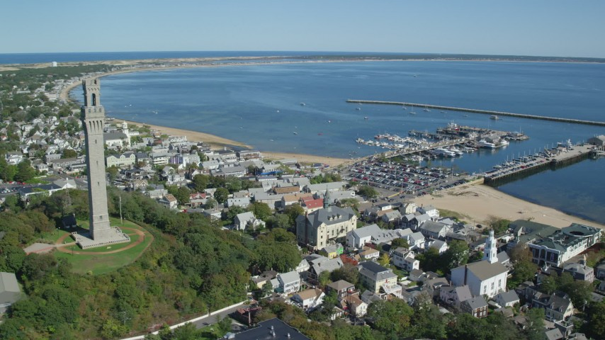 6K stock footage aerial video orbiting Pilgrim Monument, revealing piers, Provincetown, Massachusetts Aerial Stock Footage | AX143_227