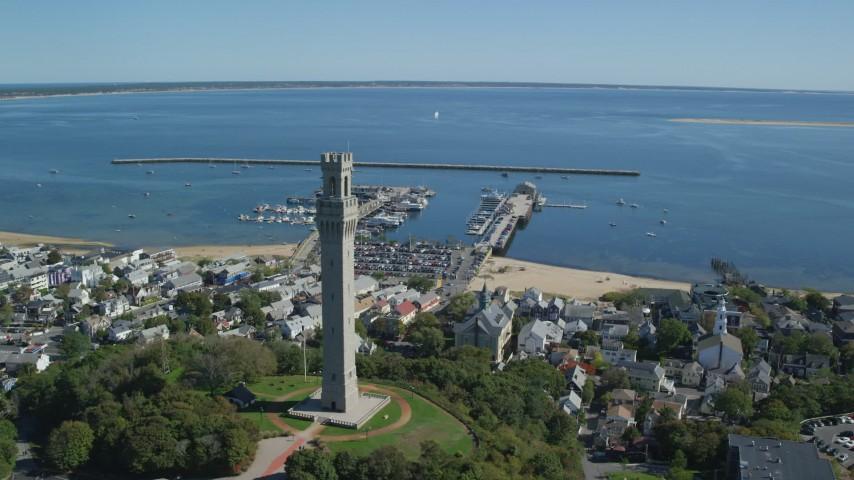 6K stock footage aerial video orbiting Pilgrim Monument, small coastal town, piers, Provincetown, Massachusetts Aerial Stock Footage | AX143_228