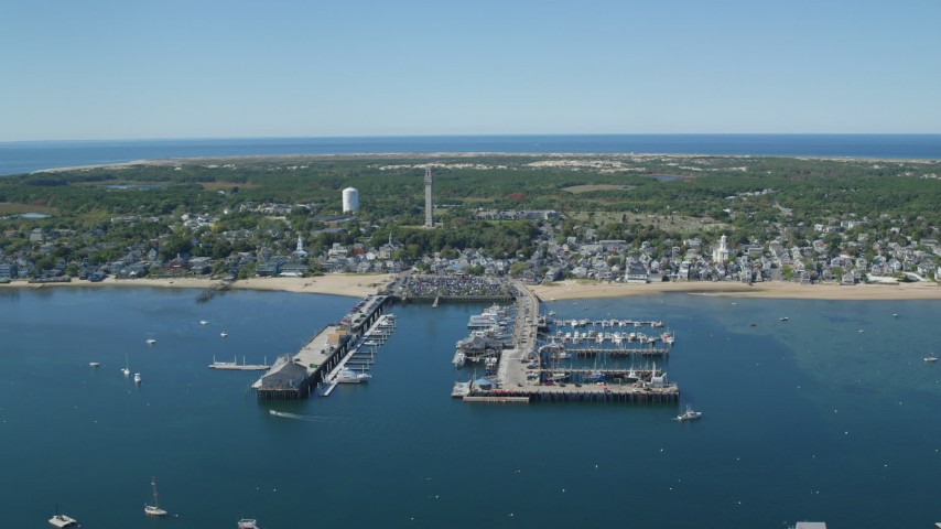 6K stock footage aerial video flying by small coastal town, piers, Cape Cod, Provincetown, Massachusetts Aerial Stock Footage | AX143_233