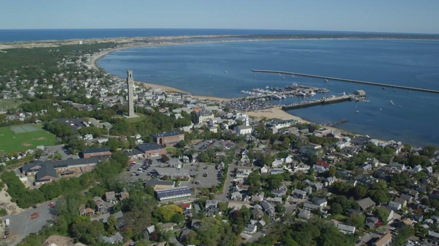 6K stock footage aerial video orbiting small coastal town, Pilgrim Monument, piers, Provincetown, Massachusetts Aerial Stock Footage | AX143_237