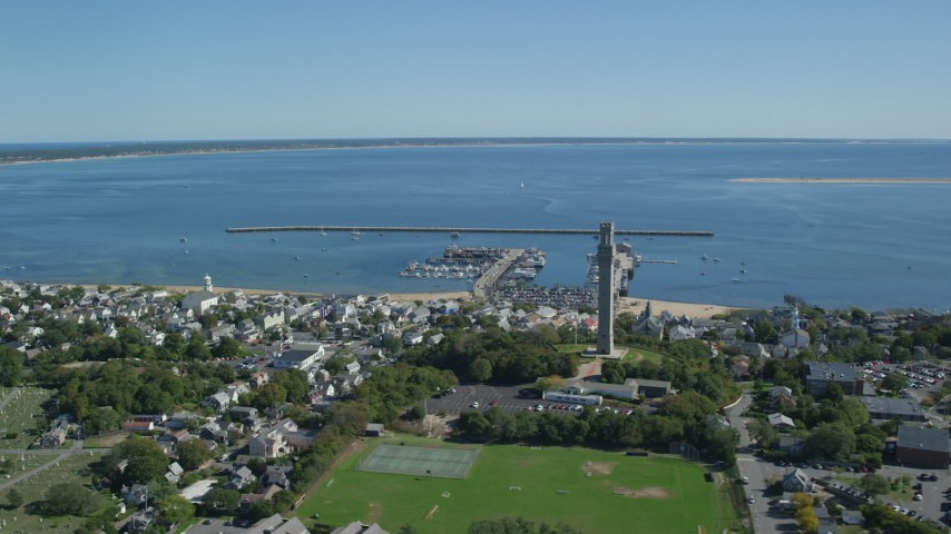 6K stock footage aerial video flying by Pilgrim Monument, tilt up to Cape Cod Bay, Provincetown, Massachusetts Aerial Stock Footage | AX143_238
