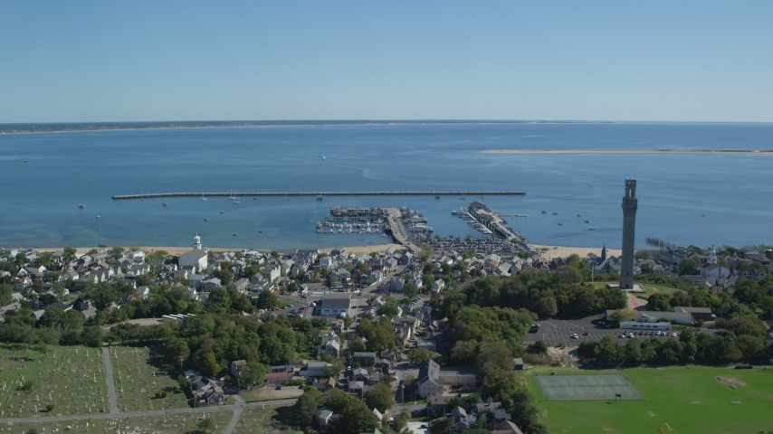 6K stock footage aerial video flying by Pilgrim Monument, piers, Cape Cod Bay, Provincetown, Massachusetts Aerial Stock Footage | AX143_239