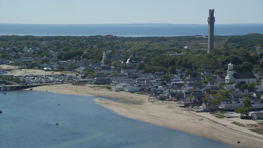 6K stock footage aerial video of a small coastal town, Pilgrim Monument, reveal piers, Provincetown, Massachusetts Aerial Stock Footage   AX143_242