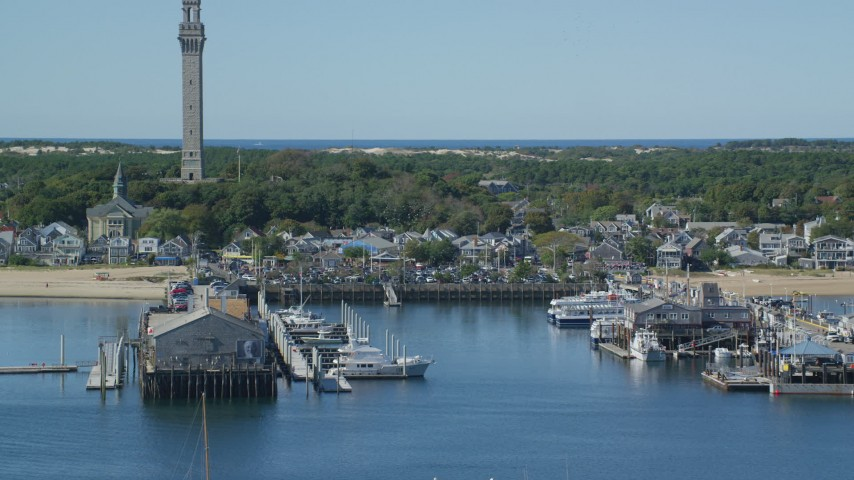 6K stock footage aerial video approaching pilgrim Monument, piers, Cape Cod, Provincetown, Massachusetts Aerial Stock Footage | AX143_247