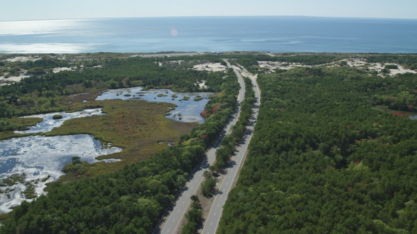 6K stock footage aerial video flying by Highway 6, coastal road, Provincetown, Massachusetts Aerial Stock Footage | AX143_251