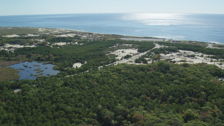 6K stock footage aerial video flying by Highway 6, coastal road, Cape Cod, Provincetown, Massachusetts Aerial Stock Footage | AX143_252