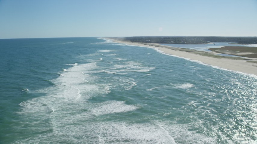 6K stock footage aerial video flying low over waves rolling into the beach, Cape Cod, Orleans, Massachusetts Aerial Stock Footage | AX144_036