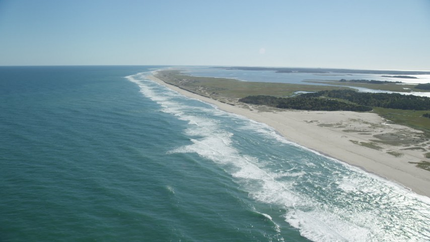 6K stock footage aerial video flying over waves, beaches, approaching marshlands, Orleans, Massachusetts Aerial Stock Footage | AX144_039