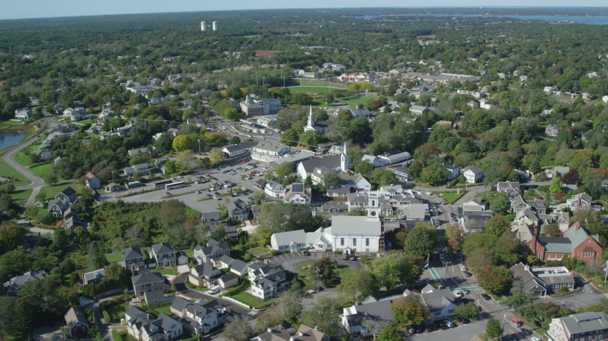 6K aerial video flying by small coastal town, churches, Cape Cod, Chatham, Massachusetts Aerial Stock Footage | AX144_050