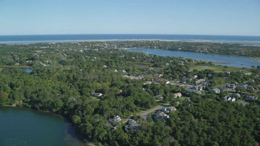 Flying by small coastal town, dense green trees, Chatham, Massachusetts Aerial Stock Footage | AX144_052