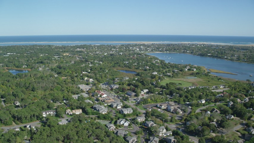 6K stock footage aerial video flying by small coastal town near Oyster Pond, Chatham, Massachusetts Aerial Stock Footage | AX144_053