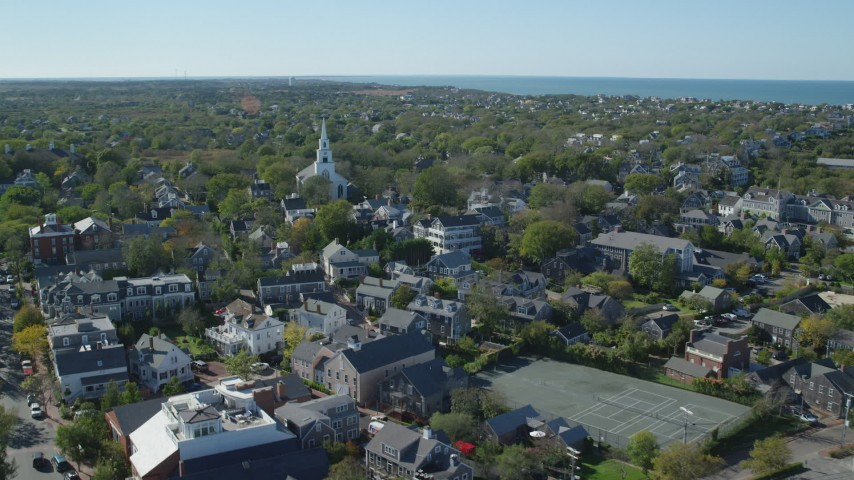 6K stock footage aerial video flying by small coastal town, approaching church, Nantucket, Massachusetts Aerial Stock Footage   AX144_083