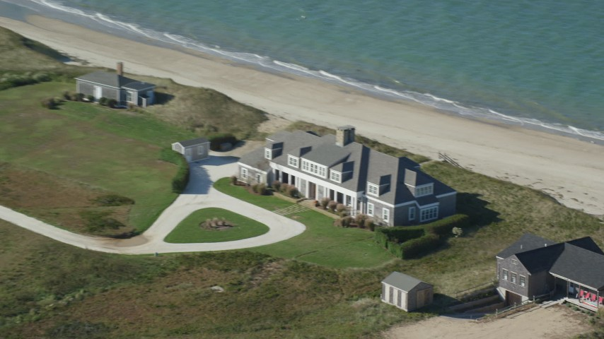 6K stock footage aerial video flying by an upscale beachfront home, Nantucket, Massachusetts Aerial Stock Footage | AX144_111