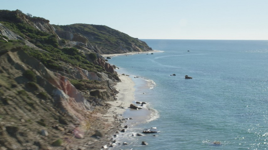 6K stock footage aerial video flying by coastal cliffs, pan to beach, Aquinnah, Martha's Vineyard, Massachusetts Aerial Stock Footage | AX144_163