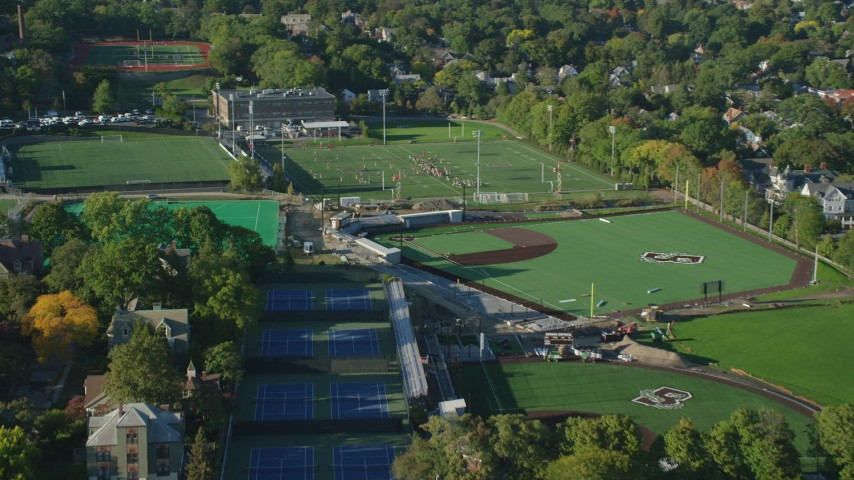 6k aerial video approaching a football practice, Brown University, Providence, Rhode Island Aerial Stock Footage | AX145_064