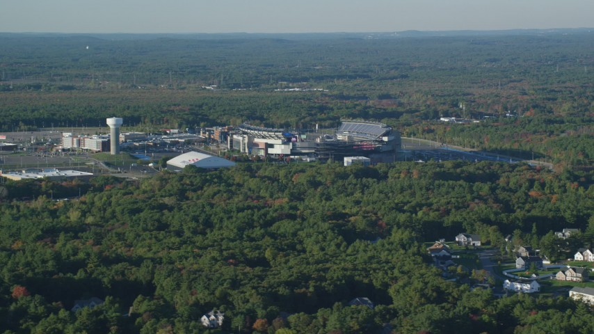 6k stock footage aerial video flying by Gillette Stadium, dense trees, autumn, Foxborough, Massachusetts Aerial Stock Footage | AX145_112