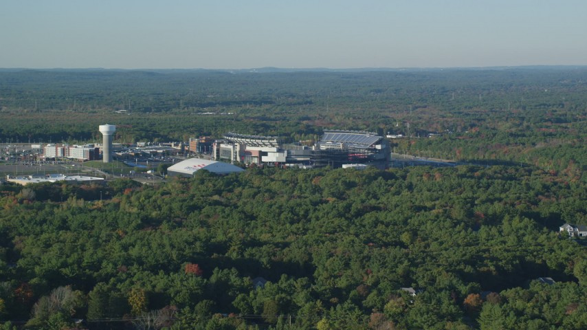 6k stock footage aerial video flying by Gillette Stadium, dense trees, autumn, Foxborough, Massachusetts Aerial Stock Footage AX145_113 | Axiom Images