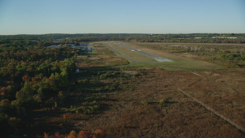 6k stock footage aerial video flying by trees, autumn, approach the Norwood Memorial Airport, Massachusetts Aerial Stock Footage | AX145_131