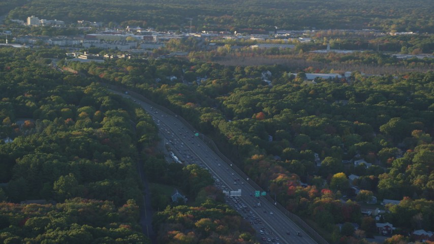 6k stock footage aerial video flying by Interstate 93, heavy traffic, autumn, Westwood, Massachusetts, sunset Aerial Stock Footage | AX146_003
