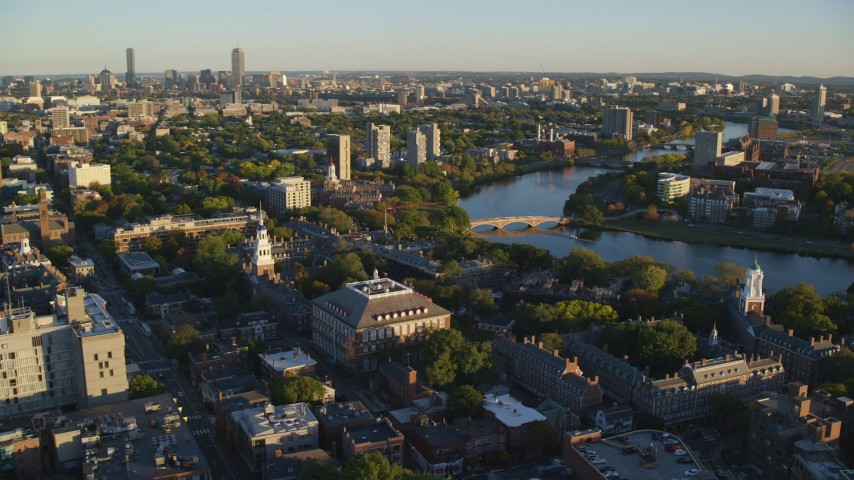 6k aerial video orbiting Harvard University, reveal Charles River, Cambridge, Massachusetts, sunset Aerial Stock Footage | AX146_021