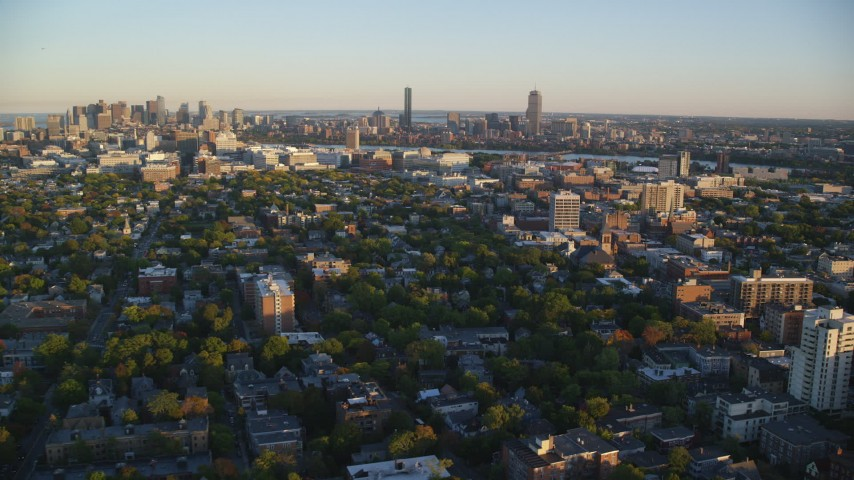 6k stock footage aerial video flying by neighborhoods, Downtown Boston skyline, Cambridge, Massachusetts, sunset Aerial Stock Footage | AX146_046