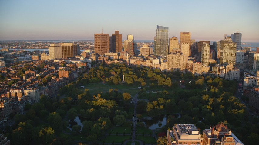 6k stock footage aerial video flying over Boston Common, approaching Downtown Boston, Massachusetts, sunset Aerial Stock Footage | AX146_065