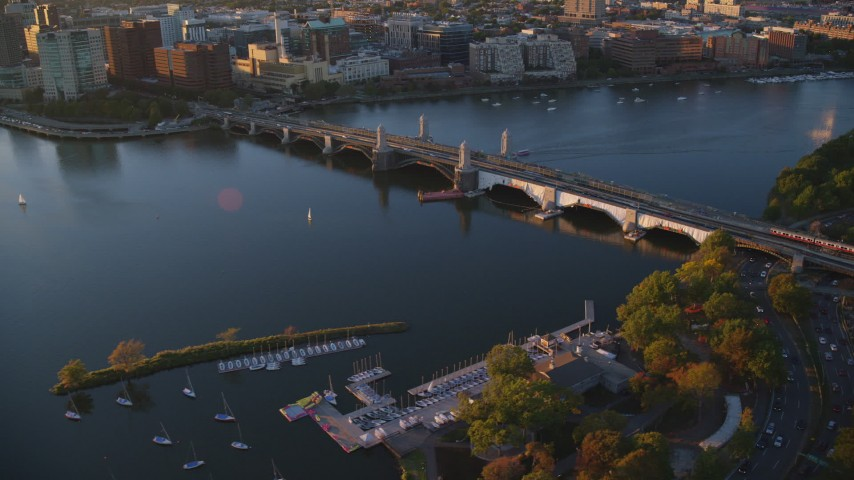 6k stock footage aerial video a commuter train crossing the Longfellow Bridge, Boston, Massachusetts, sunset Aerial Stock Footage | AX146_067