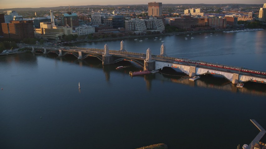 6k stock footage aerial video tracking a commuter train across the Longfellow Bridge, Boston, Massachusetts, sunset Aerial Stock Footage | AX146_068