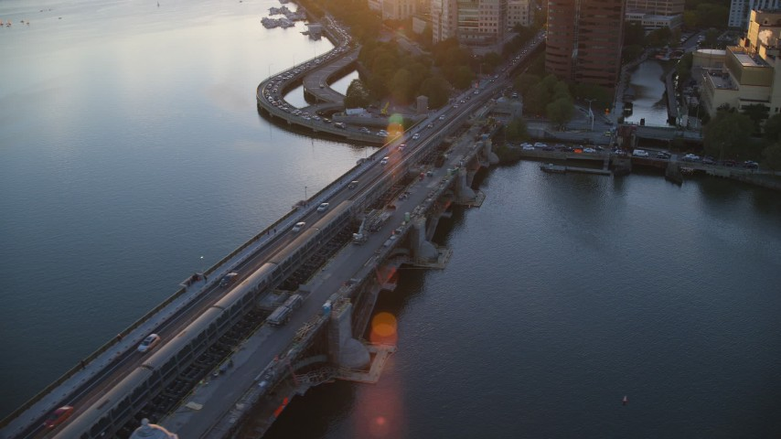 6k stock footage aerial video tracking a commuter train across the Longfellow Bridge, Boston, Massachusetts, sunset Aerial Stock Footage | AX146_070