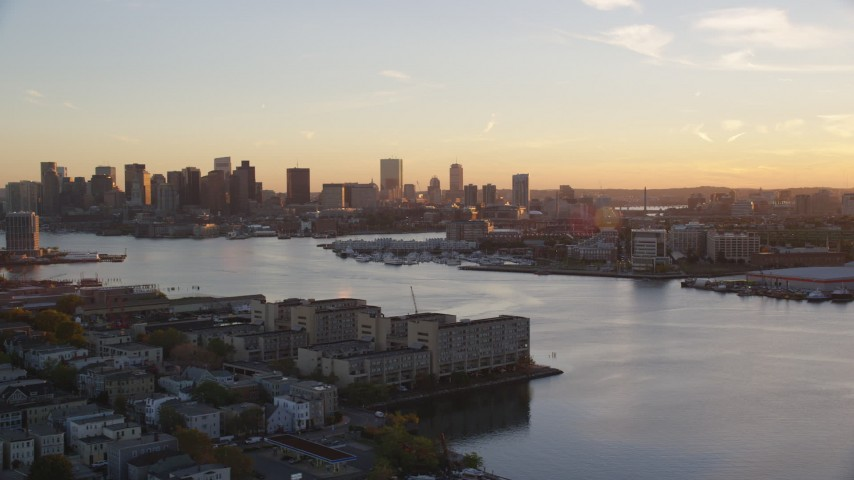 6k stock footage aerial video flying by Charles River and skyline, Downtown Boston, Massachusetts, sunset Aerial Stock Footage | AX146_075