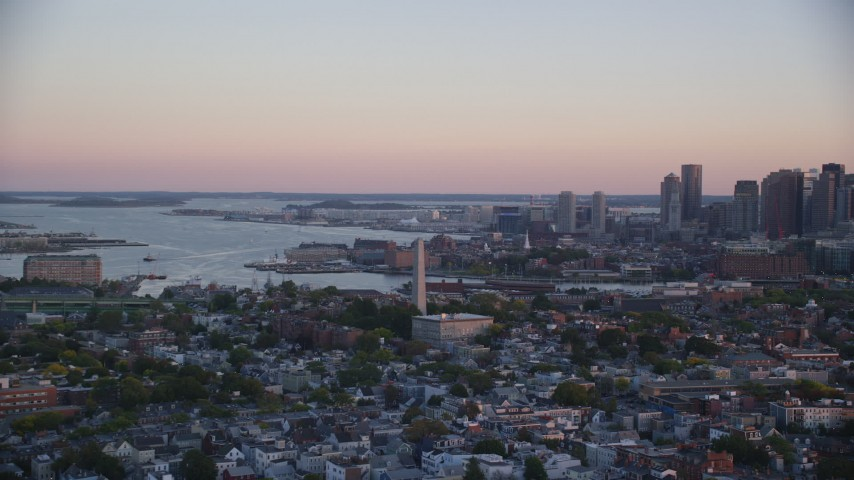 6k stock footage aerial video flying by Bunker Hill Monument, downtown skyline, Charlestown, Massachusetts, sunset Aerial Stock Footage | AX146_093