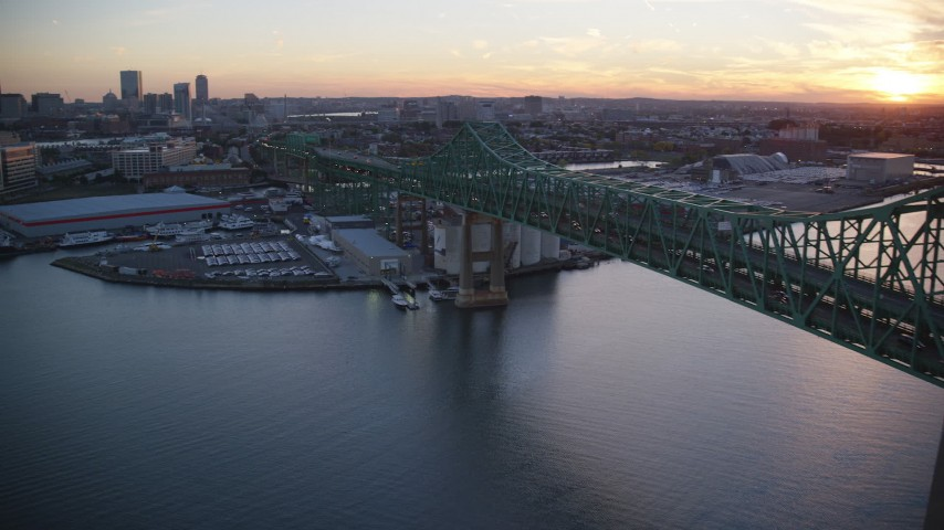 6k stock footage aerial video panning by Tobin Memorial Bridge, reveal downtown, Charlestown, Massachusetts, sunset Aerial Stock Footage | AX146_100