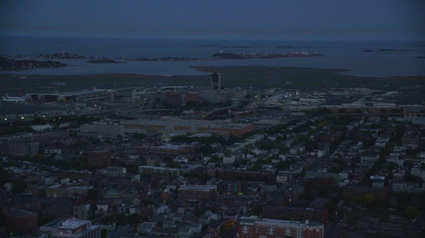 6k stock footage aerial video flying by Logan International Airport, Boston, Massachusetts, twilight Aerial Stock Footage | AX146_131